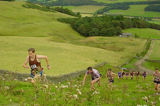 part of the cloud of brown vests (HBT) begin to climb Grieston Hill in pursuit of Colin Donnelly (out of shot)